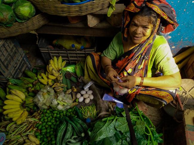 woman selling duck eggs and pumpkin flowers in Kolkata