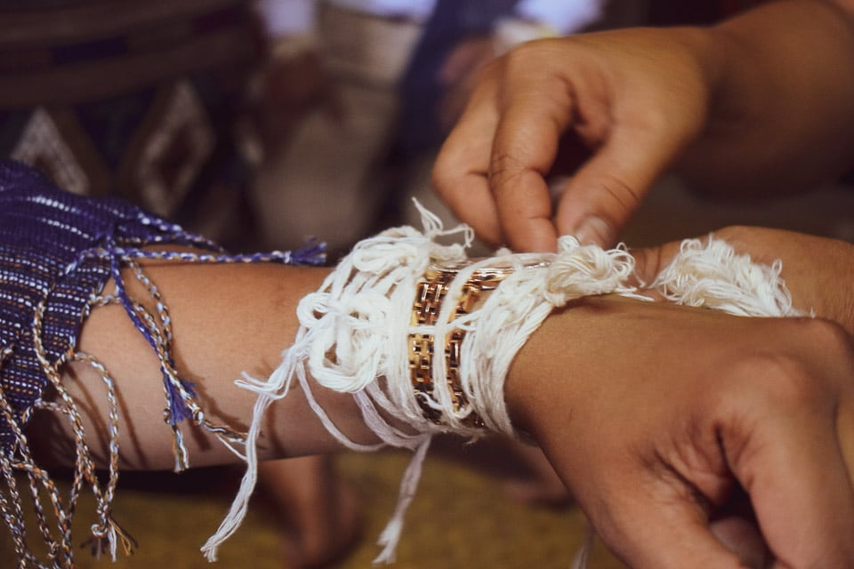 Baci threads tied on guests hand at Luang Prabang, Laos