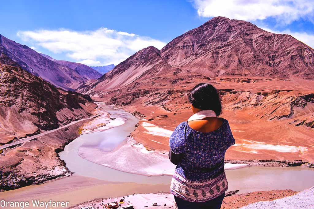 standing at Nimoo, the confluence or Sangam of Indus and Zanskar river, a day trip from Leh city: Traveling in Ladakh