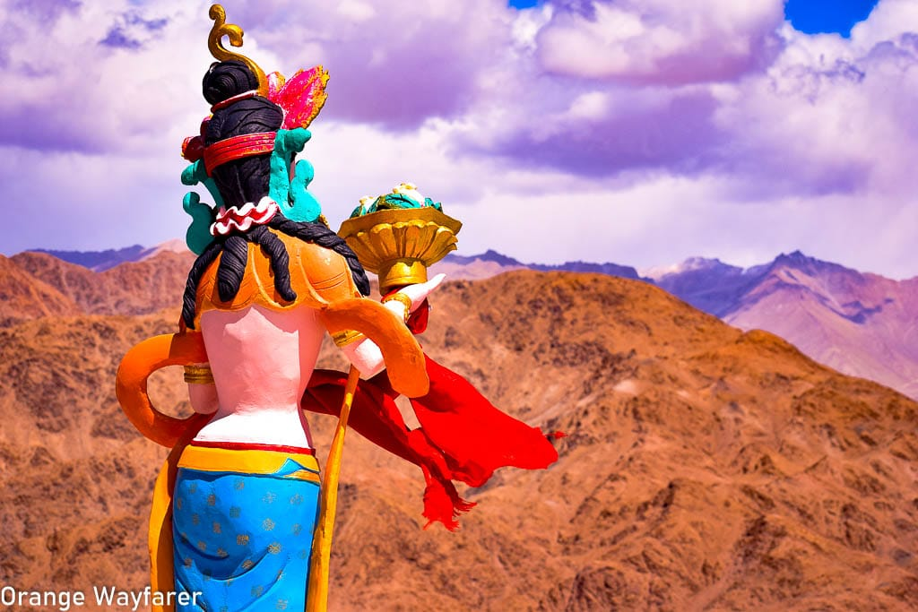A Ladakhi Buddhist Statue stand against the barren Ladakhi mountains at Hemis Monastery, a day trip from Leh: Traveling in Ladakh